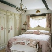 a refined vintage bedroom neutral storage units with floral patterns, a beautiful bed and a bench, a crystal chandelier and pink floral linens is lovely and chic