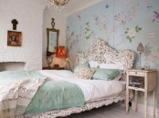 an eclectic feminine bedroom with a blue floral painted wall, a white carved bed and nightstands, a faux fireplace and artworks is very catchy