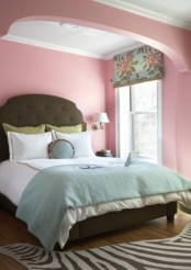 a bright feminine bedroom with pink walls, a green bed in an alcove and vintage curtains and pillows is bold and cool