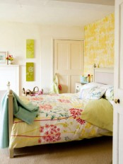 a bright feminine bedroom with an accent yellow botanical wall, neutral furniture and a faux fireplace, bright floral bedding and bold artworks