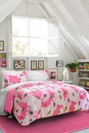 a bright attic bedroom with neutral furniture, bookshelves, a gallery wall and a bed with bright pink bedding