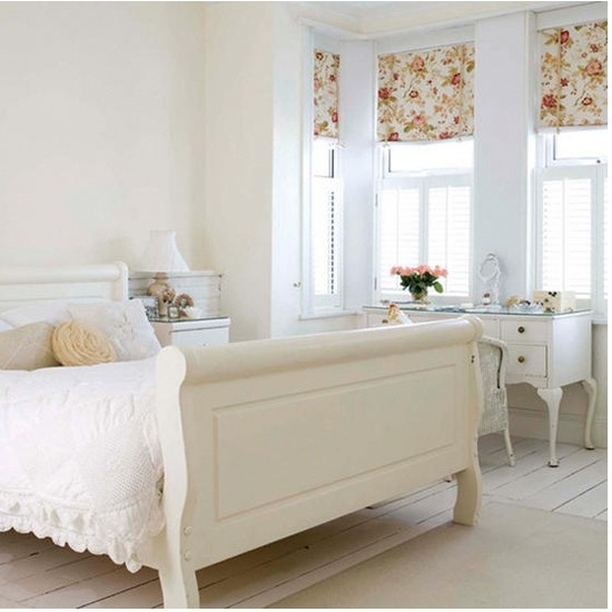 an airy feminine bedroom with elegant neutral furniture, refined lamps and accessories and floral Roman shades for an accent