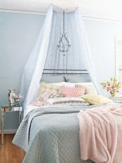 a pastel feminine bedroom with blue walls, a forged bed and a cnaopy plus a lamp, pastel blue and pink bedding