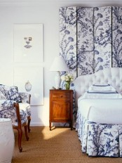 an elegant and romantic navy and white bedroom with a paneled accent wall and an upholstered bed, a chair that matches and all white or neutral is chic