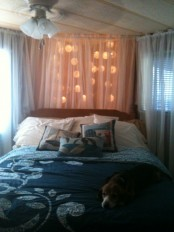 large ball shaped garland with lights hanging over the headboard and covered with a sheer curtain