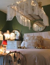 a framed window with a sheer curtain and lights hanging over the bed is a cool shabb chic idea