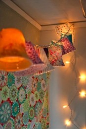 lights and a garland with colorful lampshades is a pretty vintage-inspired idea to illuminate a bedroom