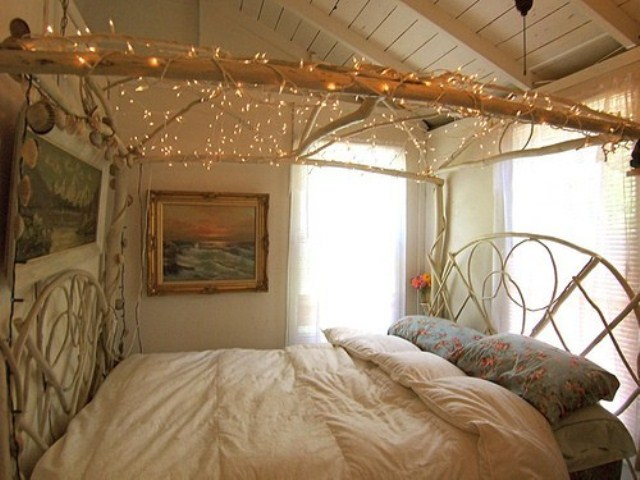 a branch frame with lights hanging over the bed for a relaxed and boho feel