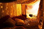 curtains with lights over the sleeping space is a cool idea for a bedroom