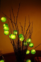 a branch arrangement with green wrapped lights is a creative and unique idea