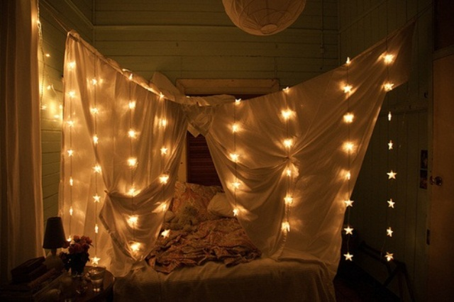 curtains around the bed with star shaped lights for a romantic feel