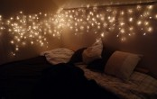 a canopy of lights over the bed is a cool and chic idea that is timeless