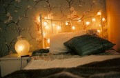 a headboard covered with lights and table lamps for a soft glow in your bedroom