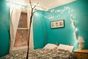 branches over the bed and lights hanging on them is a great relaxed idea for a bedroom