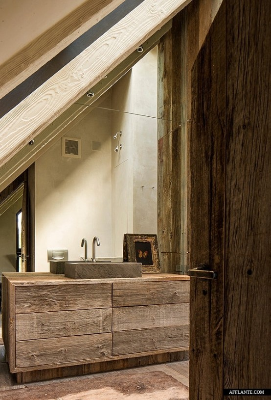 a contemporary barn bathroom clad with reclaimed wood, with a mirror wall and a reclaimed wooden vanity plus a stone sink