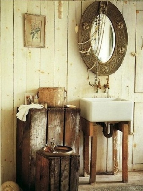 a vintage barn bathroom with whitewashed wooden plank walls, shabby chic furniture, a sink and a vintage mirror