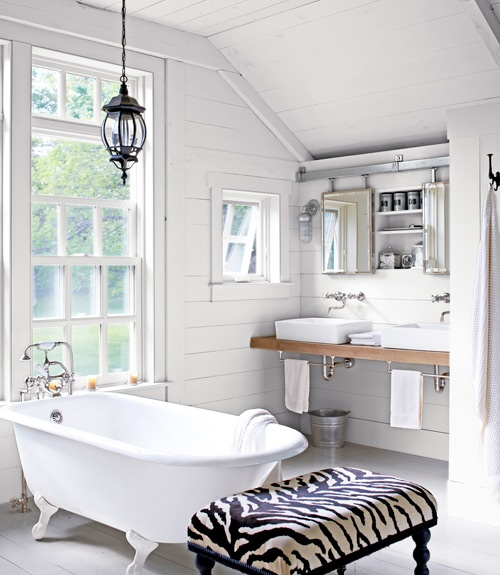 a white barn bathroom with wooden plank clad walls, a vintage lamp, a clawfoot tub, a printed ottoman and two mirrors