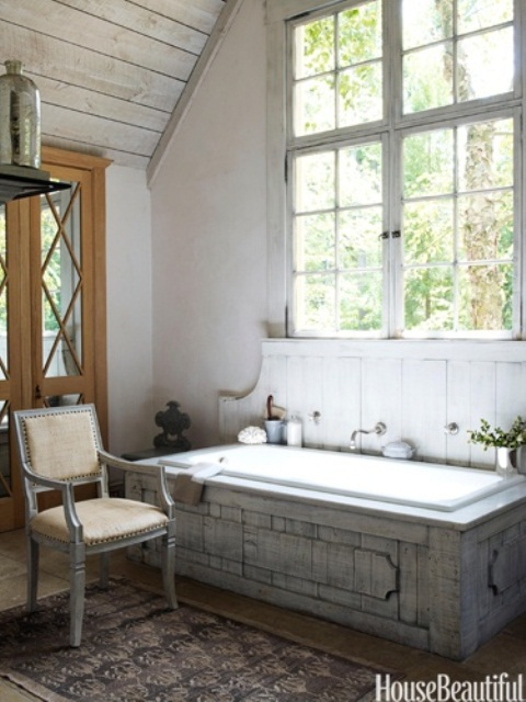 a chic neutral barn bathroom with wooden planks on the walls, a wood clad bathtub, vintage furniture and a large window to flood the space with light