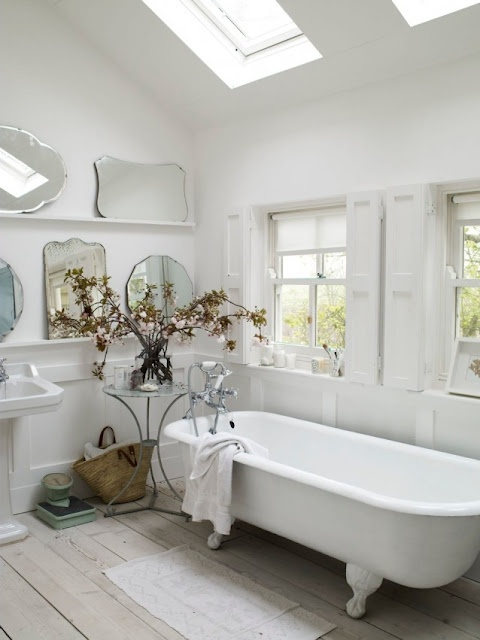 an elegant white bathroom with skylights and windows, shutters, a clawfoot tub, an arrangement of mirrors and some dried blooms