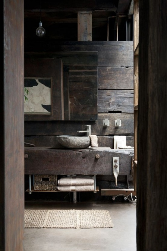 a rough barn bathroom clad with rough reclaimed wood, with a floatign vanity, a large mirror and bulbs