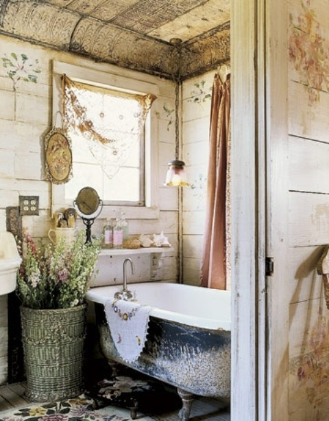 a neutral shabby chic barn bathroom clad with wooden planks, with a large basket, a clawfoot tub and a large window plus vintage accessories