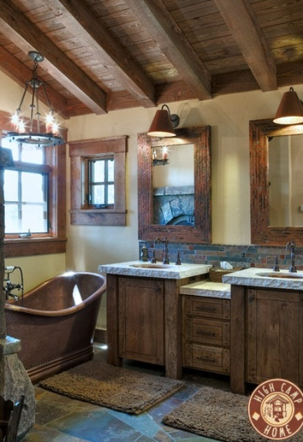 a barn bathroom with a wooden ceiling with beams, wooden furniture, a vintage metal tub and mirrors and windows in metal and wood frames