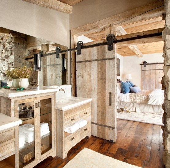 a barn bathroom with a sliding door, reclaimed wooden furniture, a large mirror and dried blooms in a vase