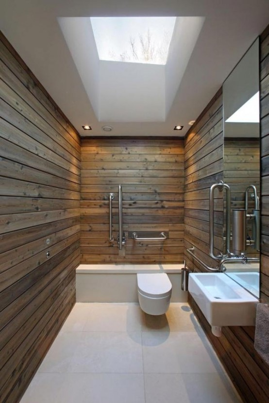 a minimalist barn bathroom clad with wooden planks, a large skylight, built-in lights, a large mirror, a wall-mounted sink
