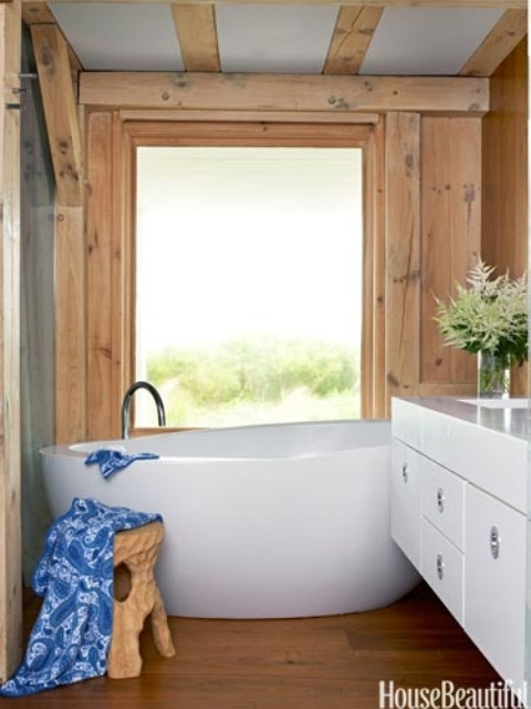 a modern barn bathroom clad with wood, with wooden beams, an oval tub and a sleek white vanity plus a large window