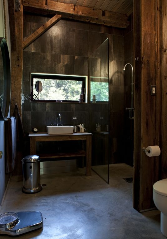 a dark barn bathroom clad with wood inspried tiles, with wooden beams, a concrete floor and a mirror in a metal frame