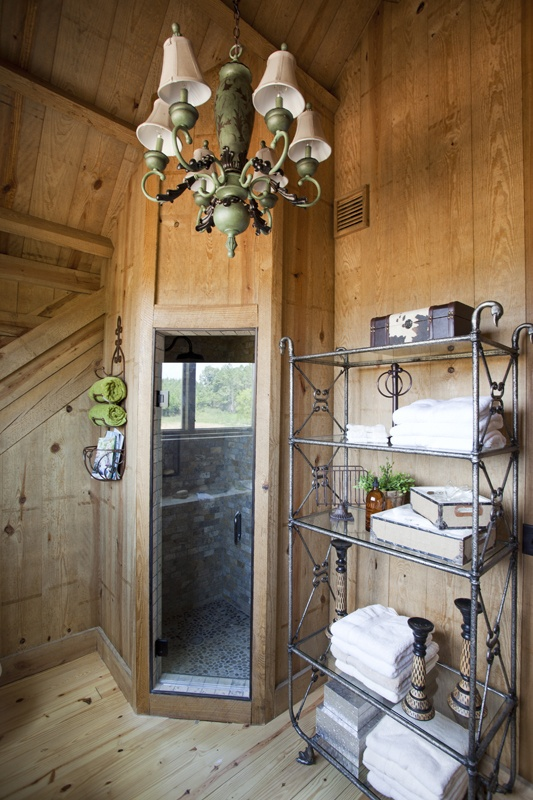 a barn bathroom clad with wood, with a shower clad with tiles, metal shelves and a refined chandelier
