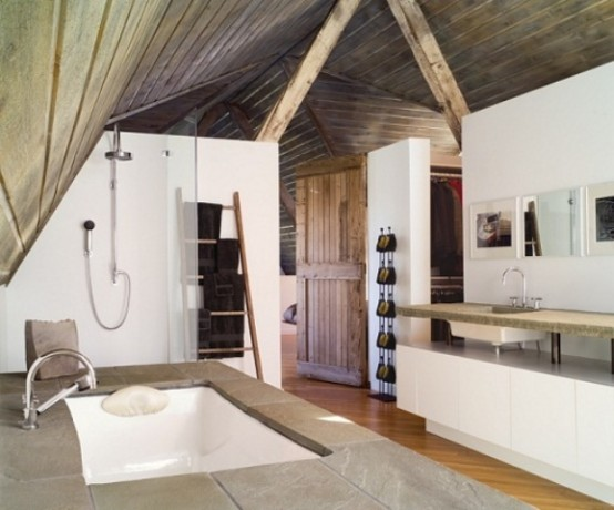 a modern rustic bathroom with white walls, a wooden ceiling with beams and a stone clad bathtub plus a raised stone countertop