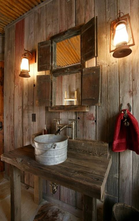 a barn bathroom clad with weathered wood, with mini windows with shutters, a metal tub sink and vintage lanterns on the wall