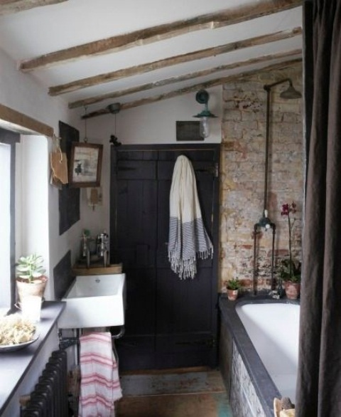 a barn bathroom with a brick wall, wooden beams on the ceiling, dark furniture and a window to brign natural light in