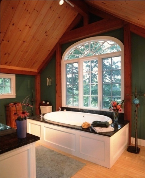 a barn bathroom with a wooden plank ceiling, wooden beams, a raised bathtub and green walls