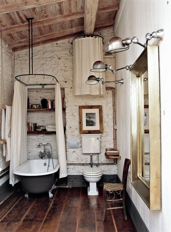 a white barn bathroom with stone walls, a wooden ceiling, wooden planks on the wall and a vintage clawfoot tub with a canopy