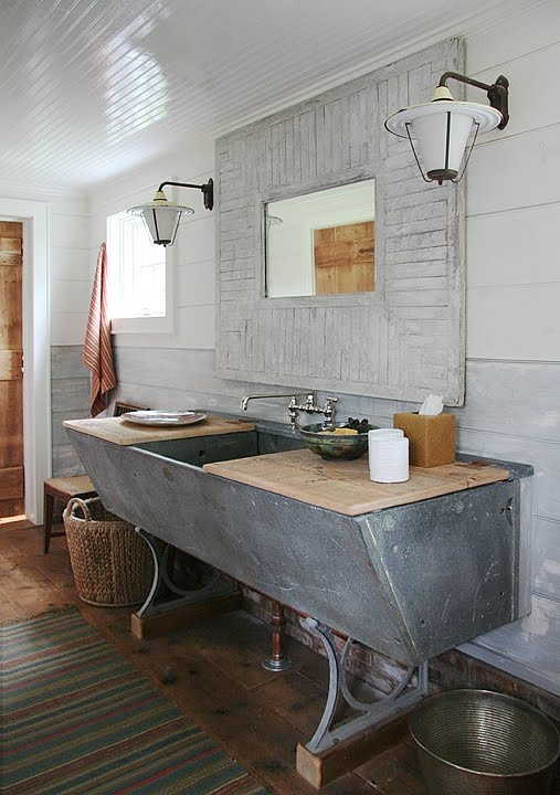 a shabby rustic bathroom with a large concrete sink, a whitewashed shabby chic mirror, baskets and rugs