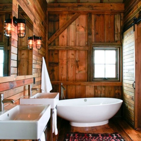 a rustic cabin bathroom fully clad with reclaimed and weathered wood, with white wall-mounted sinks, a free-standing tub and mirrors plus wall sconces