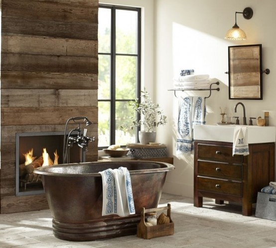 a rustic barn bathroom with a reclaimed wooden wall, wooden furniture, a built-in fireplace and a vintage metal bathtub