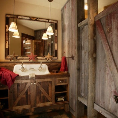 a rustic bathroom clad with reclaimed wood, with a vintage mirror, a reclaimed wooden vanity and bright towels