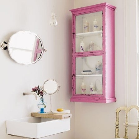 a chic guest toilet with a pink storage unit, a wall-mounted sink and some mirrors