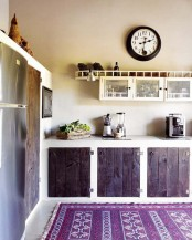 a stained kitchen with white framing and a colorful printed rug feels cozy and very boho at the same time