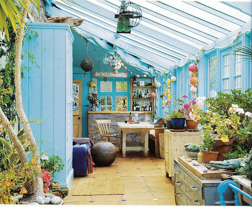 Rustic sunroom In a cottage. Lovely sky blue walls and decorations make the space cool and fun.