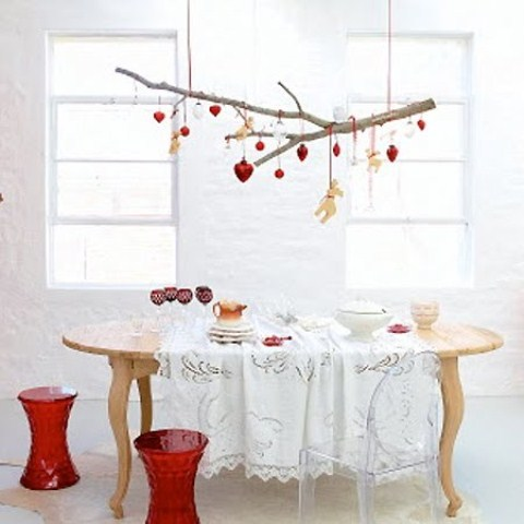 a branch with red and gold Christmas ornaments, red stools and gold goblets for a Scandi dining space