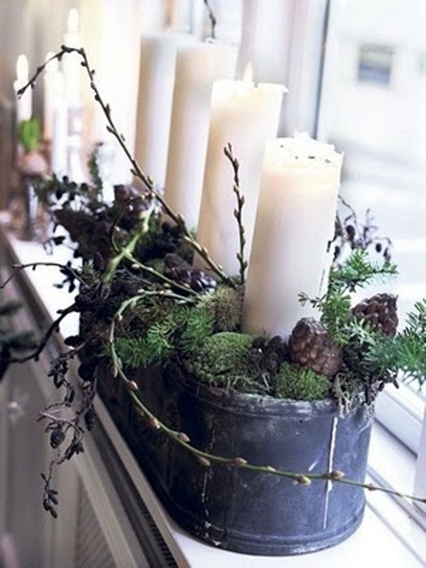 a Scandinavian Christmas decoration of a tin can with moss, branches and candles plus pinecones for a Nordic feel