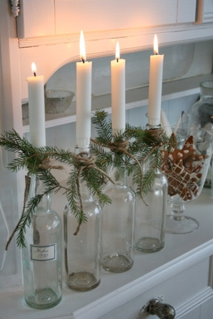 bottles as candle holders wrapped with evergreens and with candles in them for a cozy rustic touch