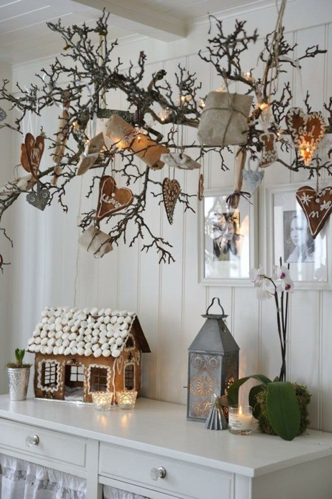 large branches attached to the ceiling, with gingerbread hearts and gift boxes and a large gingerbread house on the table for a Nordic feel