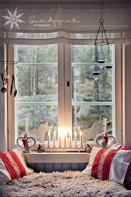 red and white linens, faux fur, a white curtain with Nordic decor and a candleholder with severla candles plus wooden horses