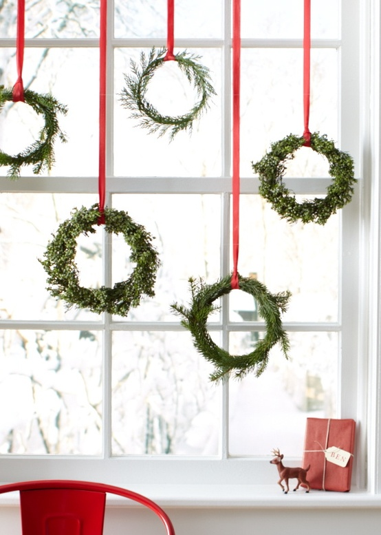 a whole arrangement of evergreen wreaths hanging on red ribbons for a chic and natural Scandinavian feel