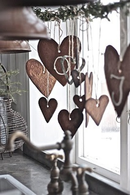 an evergreen branch with heart gingerbread cookies hanging down from it is a cozy Nordic feel in the space